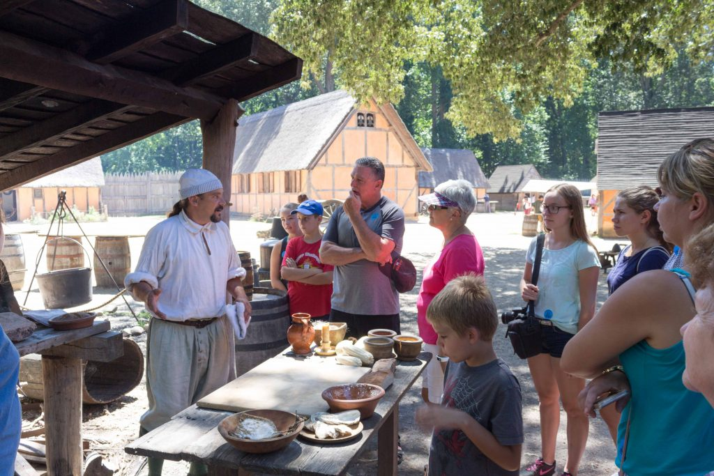 A docent at Jamestown Settlement's fort shows onlookers how he prepares food for the Virginia Company outpost. (Kevin Kaiser | Travel Beat Magazine)