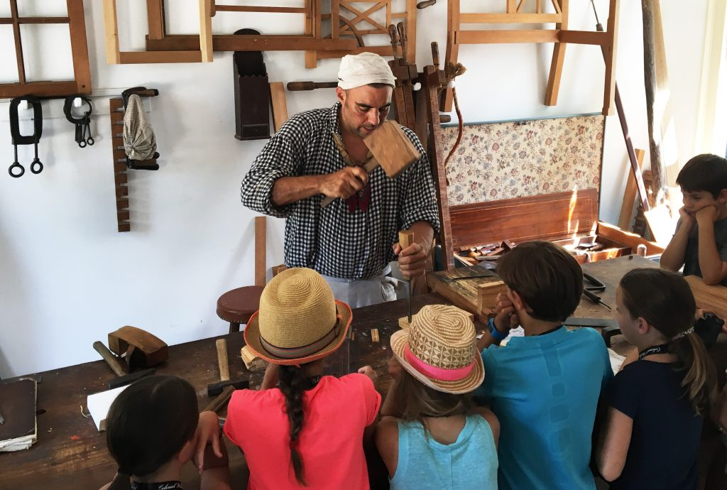 A living history docent shows how he creates wood materials and frames by carefully working the wood into different configurations. This is one of the many Colonial buildings that you must purchase a Colonial Williamsburg pass to be able to see. (Kevin Kaiser | Travel Beat Magazine)