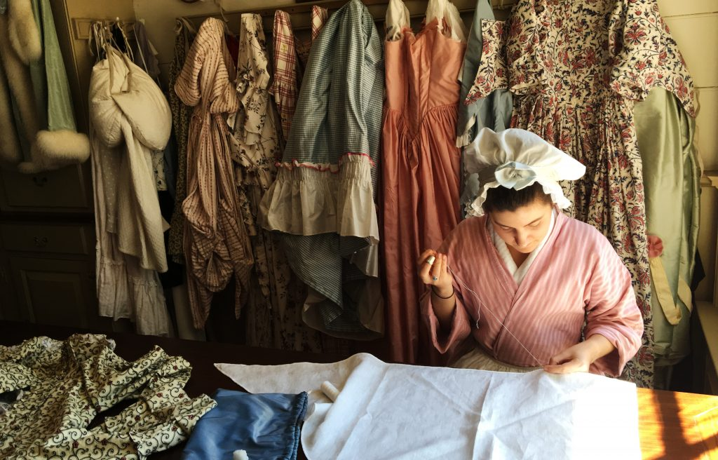 Learn all about the ladies' fashions of the Colonial period by stopping in to a working shop. This seamstress is working on a pattern by the light of the window. (Kevin Kaiser | Travel Beat Magazine)
