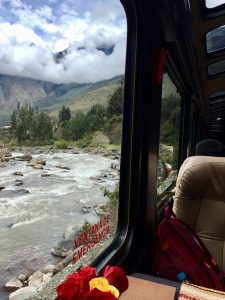 Passing the Urubamba River by train, you see mountains and terraced Incan ruins in the distance. (Kevin Kaiser | Travel Beat Magazine)