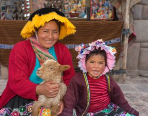 A mother and child pose for a photo for tourists in the Pisac square. (Kevin Kaiser | Travel Beat Magazine)